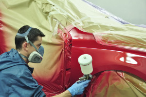 Qualified technician working on the auto body paint
